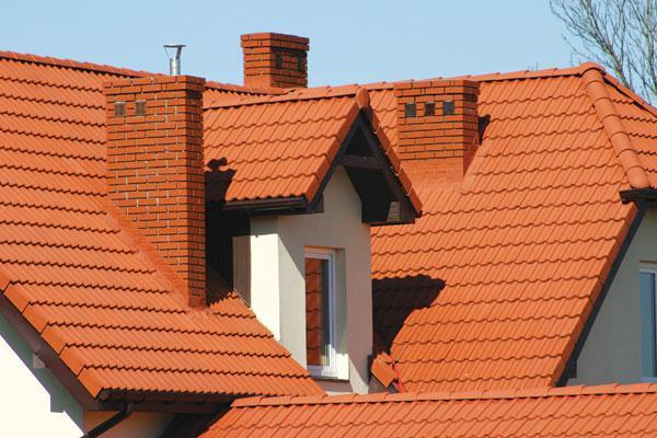 Крыша дома с кирпичным дымоходом